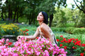 Beautiful girl in park with colorful flowers Stock Photography