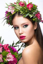 Beautiful girl with perfect skin and bright floral wreath on her head picture taken in the studio a white background Stock Photo