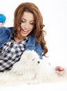 Beautiful girl with perfect skin and long wavy hair with a fluffy white dog on a white background Royalty Free Stock Photo
