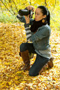 Beautiful girl photographer knee on nature (backli Stock Images