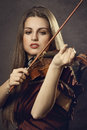 Beautiful girl plays a fiddle dressed with an elegant red dress Royalty Free Stock Photos