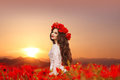 Beautiful girl in poppies field at sunset. Happy smiling teen po Royalty Free Stock Photo