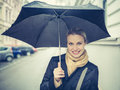 Beautiful girl is posing at street holding an umbrella during a spring rainy weather Royalty Free Stock Images