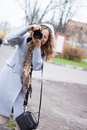 Beautiful girl press photographer or tourist shooting looking at Stock Photo