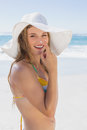 Beautiful girl putting spf on nose on the beach smiling at camera a sunny day Royalty Free Stock Images