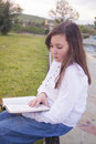 Beautiful girl reading a book in park Stock Photos