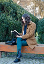 Beautiful girl reading book in the park in spring Royalty Free Stock Photo