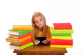 Beautiful girl reading e-book surrounded by books Stock Photo