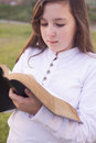 Beautiful girl reading holy bible in a park Stock Images