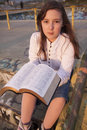 Beautiful girl reading holy bible on a sun set Royalty Free Stock Photo