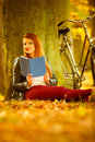 Beautiful girl is reading under the tree. Royalty Free Stock Photo