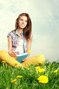 Beautiful girl reads the book lies on meadow and Royalty Free Stock Images