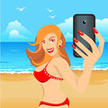 Beautiful girl in red bikini on beach makes selfie Royalty Free Stock Photo