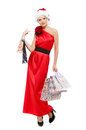 Beautiful girl in a red dress and hat of santa claus with shopping bag isolated Royalty Free Stock Photo