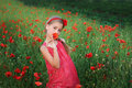 Beautiful girl in red dress walks at poppy field Royalty Free Stock Photo