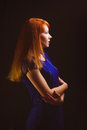 Beautiful girl red haired woman looking away dark is in a blue dress on a black background studio Royalty Free Stock Images