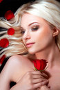 Beautiful girl with red roses in her blond hair.. Royalty Free Stock Image