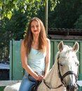 A beautiful girl is riding a beautiful white horse. Royalty Free Stock Photo