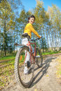 Beautiful girl riding bicycle against autumn nature Stock Image