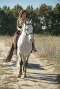 Beautiful girl riding on the white horse in a Royalty Free Stock Photo