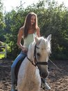 A beautiful girl is riding a white horse. Royalty Free Stock Photo