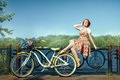 Beautiful girl on the riverbank next to her is a bicycle bike basket with flowers Royalty Free Stock Image