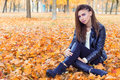 Beautiful girl in rock style with bright makeup in white jacket and black pants and boots in a leather jacket sitting in the Park Royalty Free Stock Photo