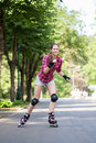 Beautiful girl on rollerblades a portrait of a with riding in a park Royalty Free Stock Images