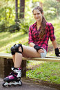 Beautiful girl on rollerblades a portrait of a with who is sitting a branch in a park Royalty Free Stock Images