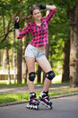 Beautiful girl on rollerblades a portrait of a with who is sitting a branch in a park Stock Photos