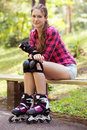 Beautiful girl on rollerblades a portrait of a with who is sitting a branch in a park Stock Images