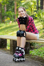 Beautiful girl on rollerblades a portrait of a with who is sitting a branch in a park Royalty Free Stock Photos