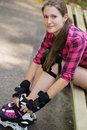 Beautiful girl on rollerblades a portrait of a with who is sitting a branch in a park Stock Photo