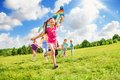 Beautiful girl run with kite together with friends happy cute smiling and other kids boys and girls running in the park on sunny Stock Images