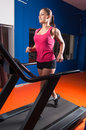 Beautiful girl running in the gym smiling on treadmill Stock Photos