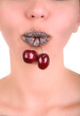 Beautiful girl's lower part of face with two red cherries in mouth Royalty Free Stock Photo