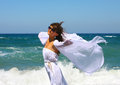 The beautiful girl in the sea in white at developing clothes on a breeze Royalty Free Stock Images