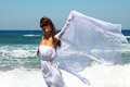 The beautiful girl in the sea in white at developing clothes on a breeze Stock Photo