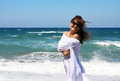 The beautiful girl in the sea in white at developing clothes on a breeze Stock Photos
