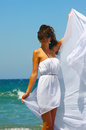 The beautiful girl in the sea in white at developing clothes on a breeze Stock Image