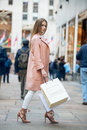 Beautiful girl with shopping bags going to the store on New York City street Royalty Free Stock Photo