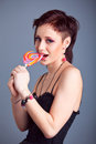 Beautiful girl with short hair licking a lollipop Royalty Free Stock Photo