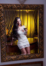 The beautiful girl in a short white dress looking into mirror young woman wearing old hotel Stock Photography