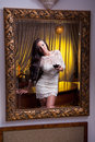 The beautiful girl in a short white dress looking into mirror young woman wearing old hotel Royalty Free Stock Photo