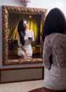 The beautiful girl in a short white dress looking into mirror young woman wearing old hotel Royalty Free Stock Image