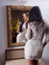 The beautiful girl in a short white dress looking into mirror young woman wearing old hotel Stock Photos