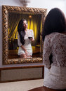 A beautiful girl in a short white dress reflected into a into mirror young woman wearing the old Royalty Free Stock Photos