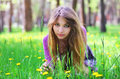 Beautiful girl sit down on the grass with flowers