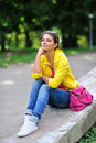 Beautiful girl sit in a park with hand on chin outdoors Royalty Free Stock Photography