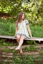 Beautiful girl sits on the boards of bare feet dangling Stock Photo